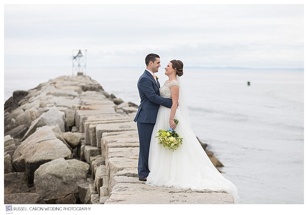 bride and groom standing on the Kennebunkport Maine breakwater