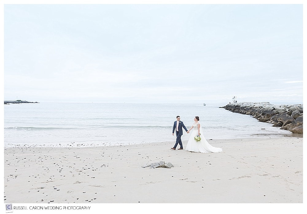 bride and groom walking on Colony Beach in Kennebunkport, Maine