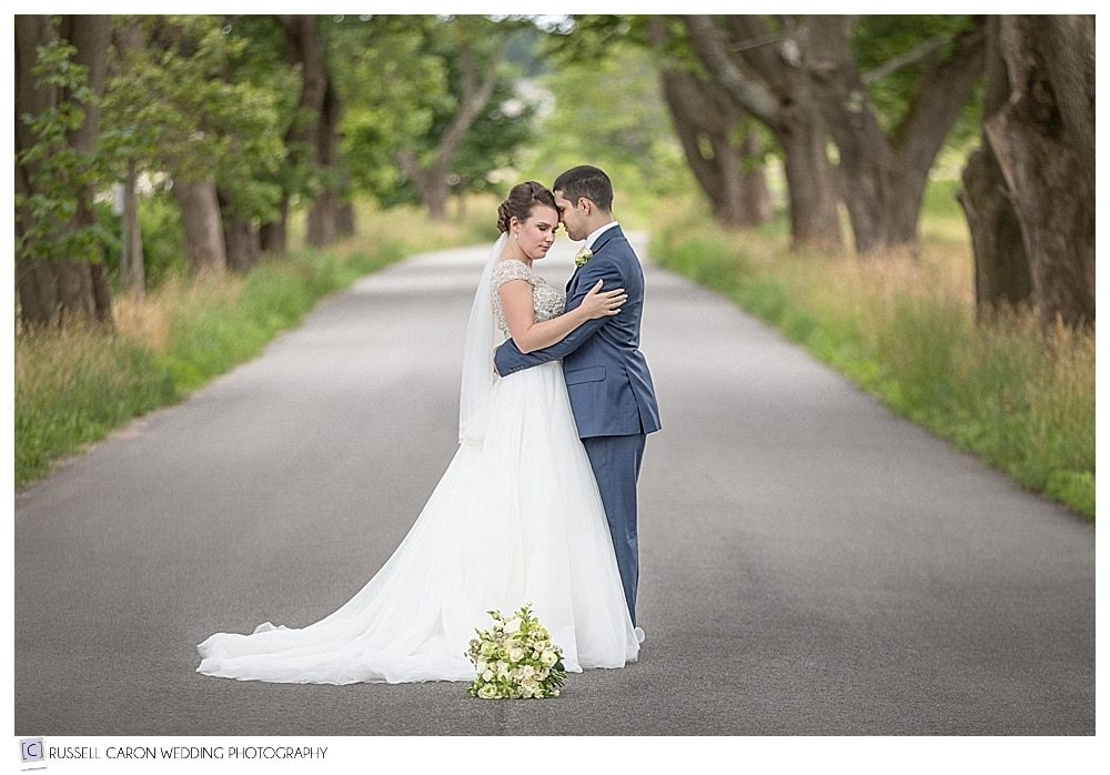 bride and groom standing in road with trees