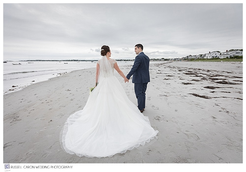 bride and groom walking along the water at Goose rocks beach, kennebunkport
