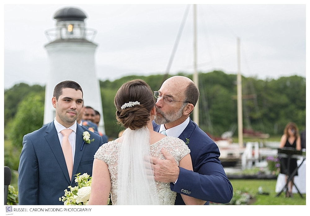 bride kisses her father as the groom looks on