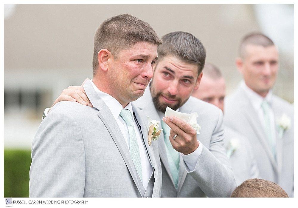 Emotional groomsman offering tissue to groom