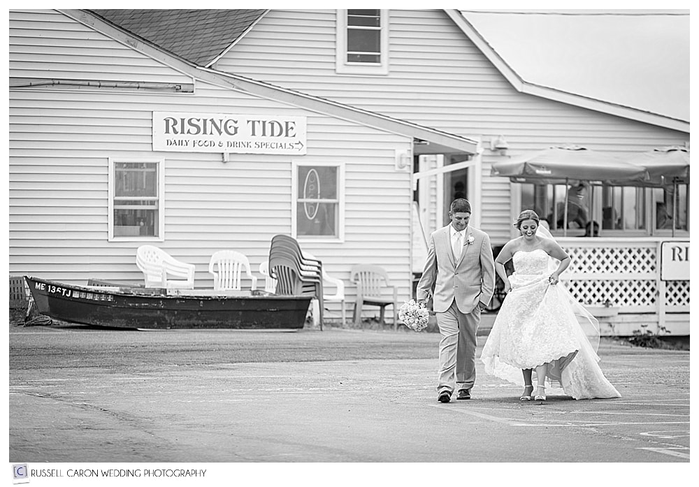 Bride and groom walking past Rising Tide Restaurant