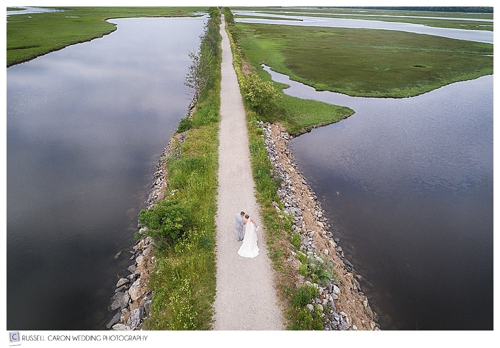 Bride and groom walking on Scarborough Marsh Eastern Trail by Maine drone wedding photographers
