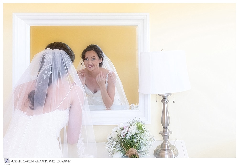 Bride checking herself in a mirror