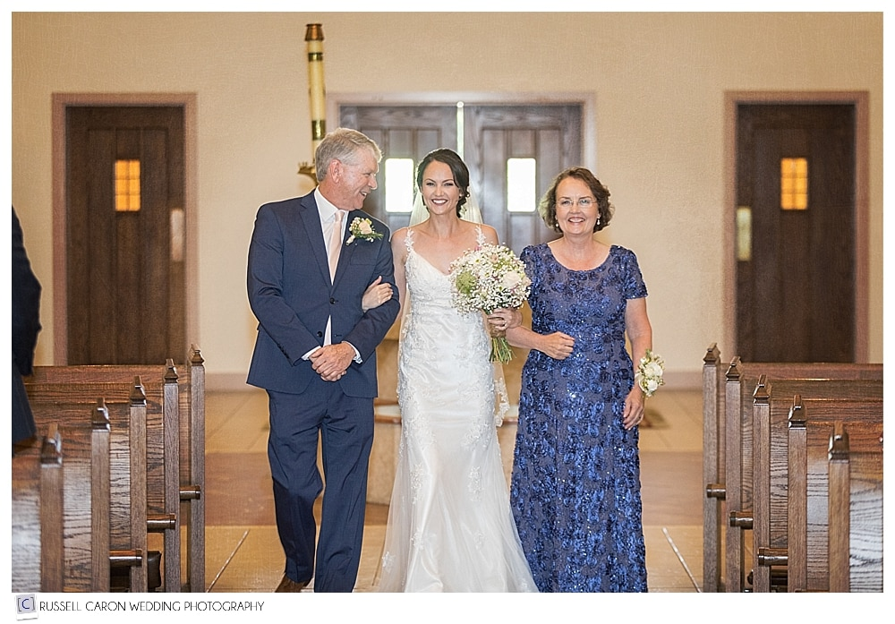 bride coming down the aisle with her parents