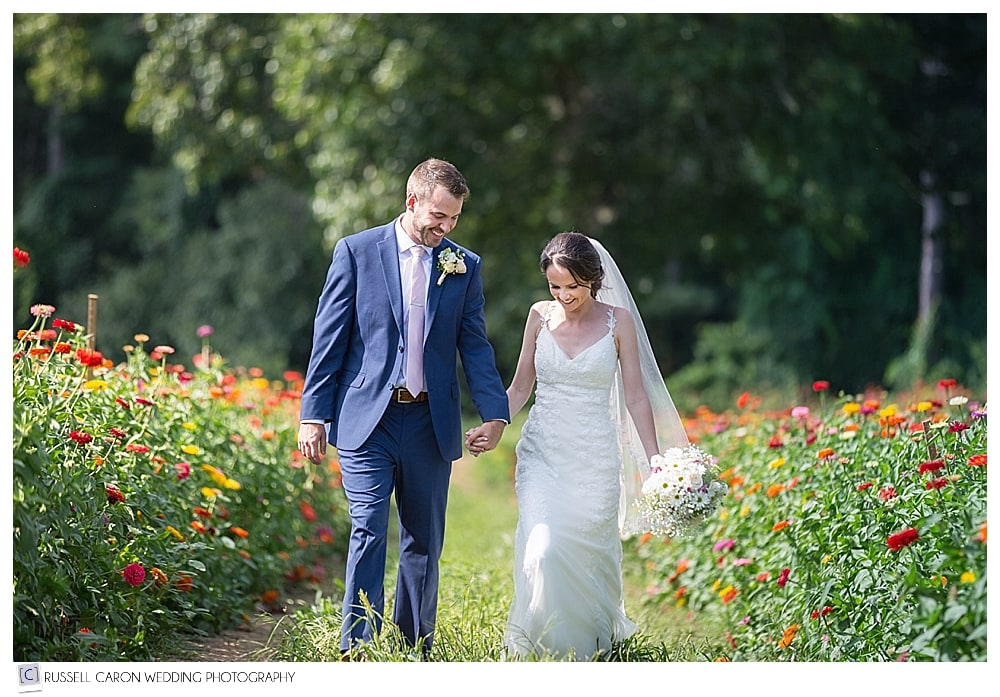 bride and groom walking among the flowers at their Parlee Farms wedding
