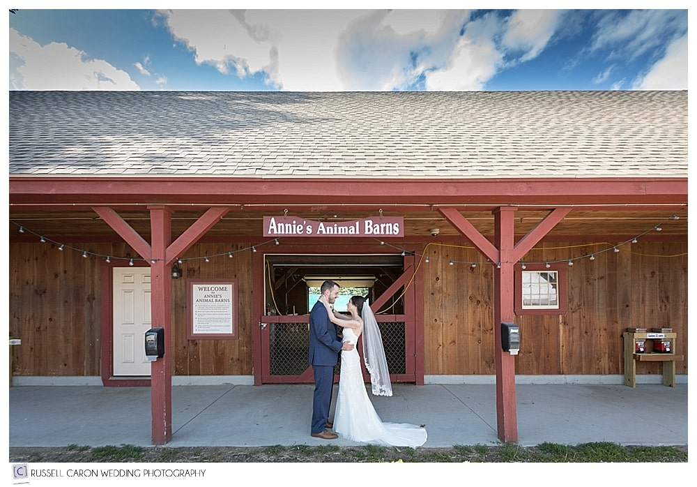 bride and groom in front of the animal barns, named after the bride
