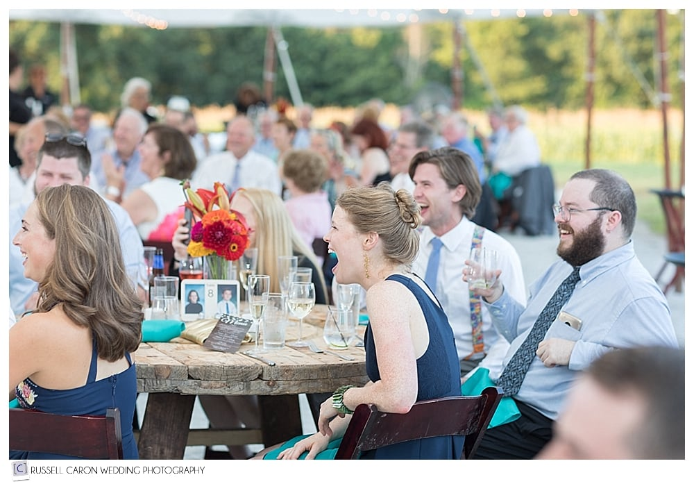 Guests laughing during wedding toasts