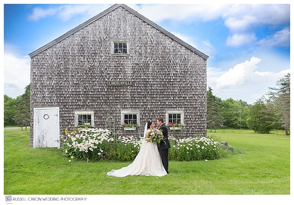 bride-and-groom-in-front-of-weathered-barn