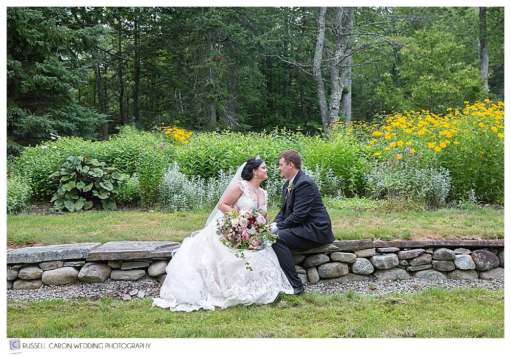 bride-and-groom-sitting-on-stone-wall