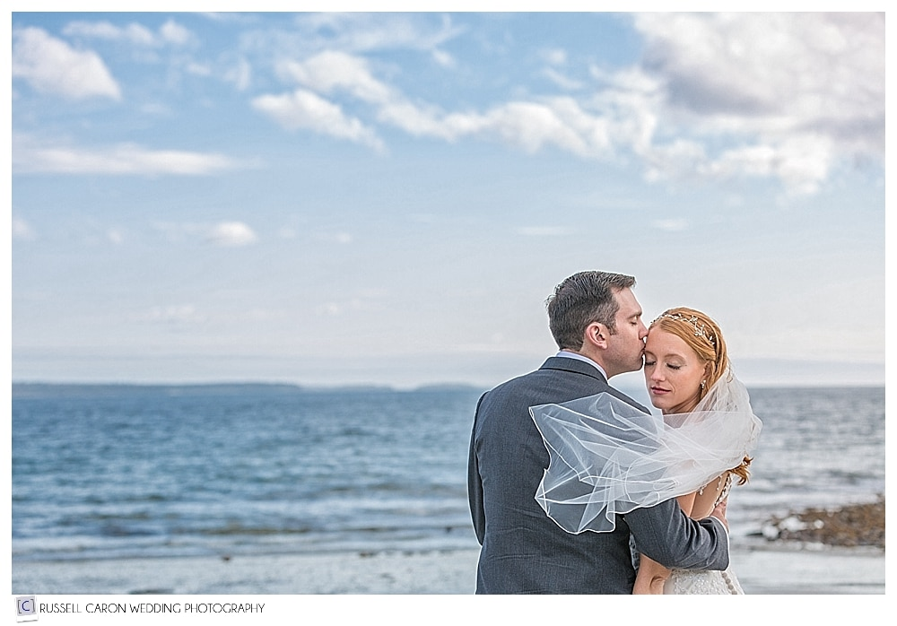 bride and groom at the beach with blowing veil