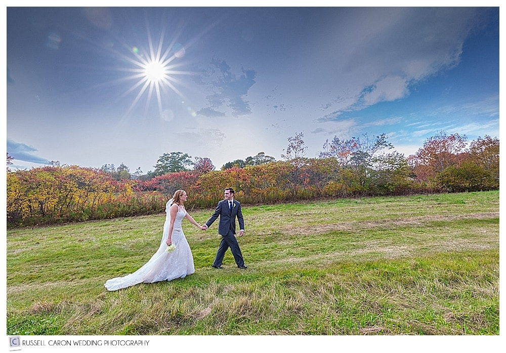 groom leading the bride up a hill surrounded by fall foliage