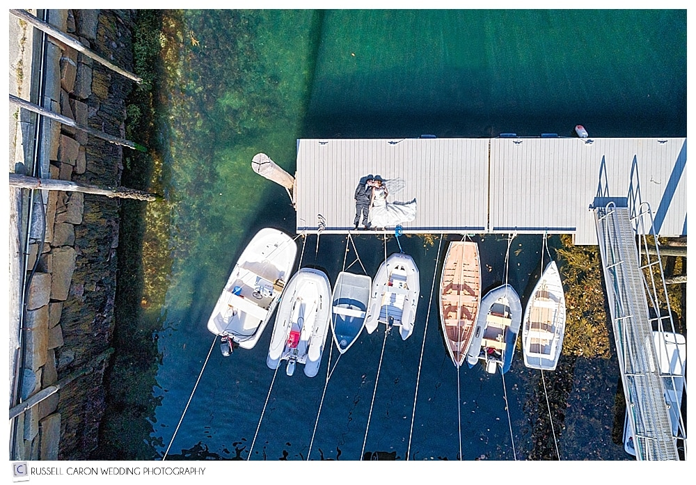 Maine drone wedding photography of bride and groom on the dock at Rockport Harbor, Maine