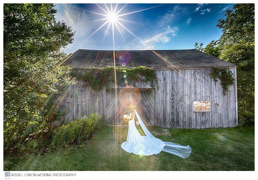 sunburst photo of bride in front of vintage barn