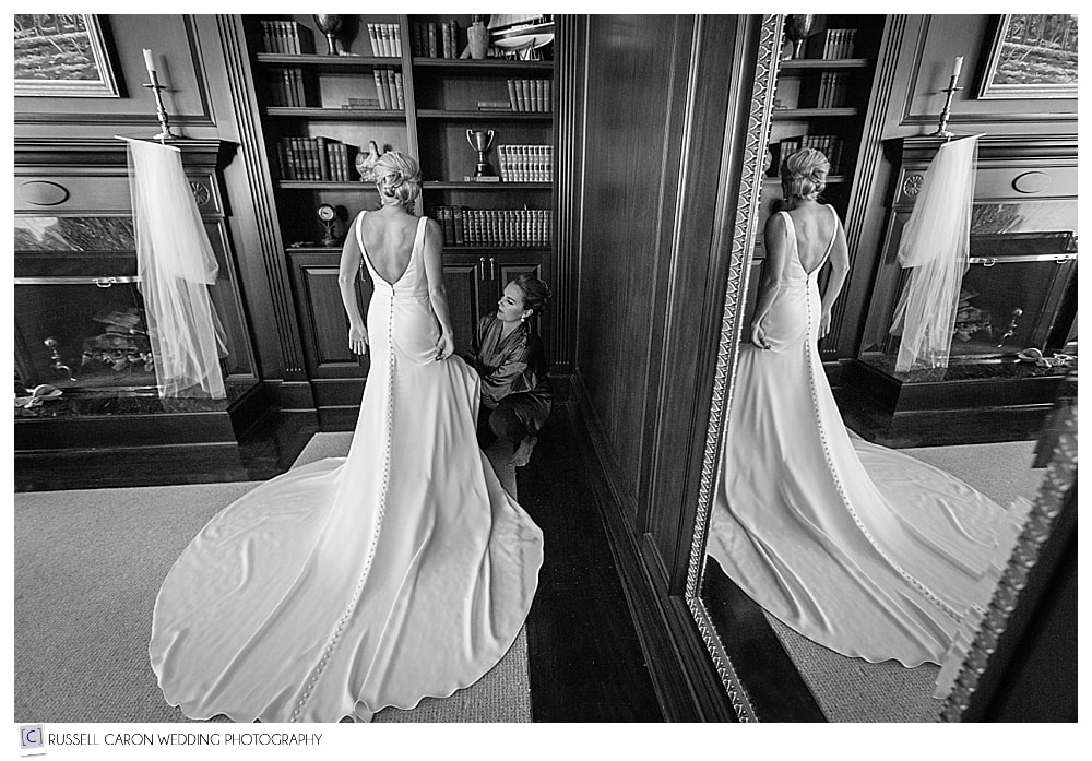 bride getting into wedding dress, in the board room at Point Lookout