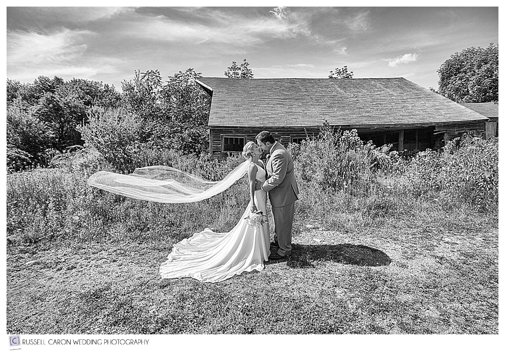 bride and groom in front of old barn