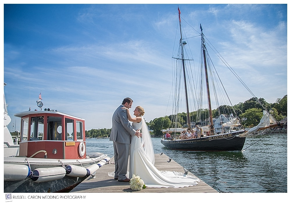 bride and groom in Camden Harbor Maine, with schooner sailing by