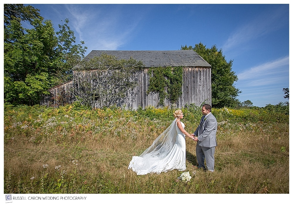 bride and groom in a field in front of old barn at Point Lookout wedding
