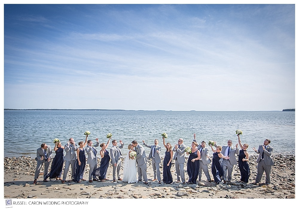 bridal party cheering bride and groom kissing