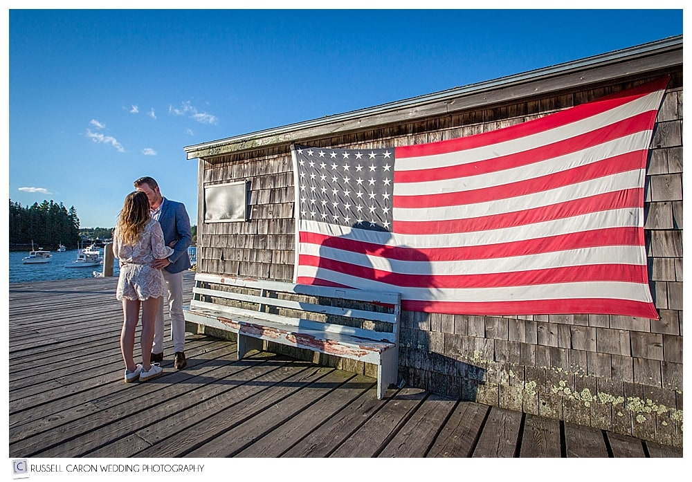 man and woman kissing on dock in Port Clyde Maine, with american flag