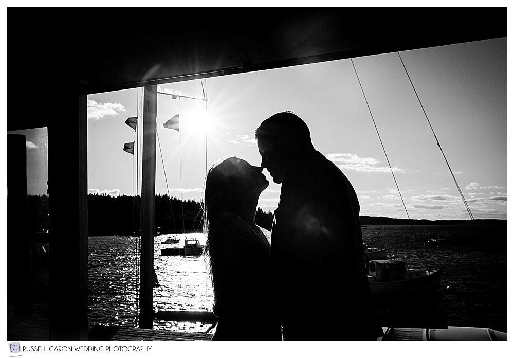 silhouette of man and woman standing together on a fishing dock