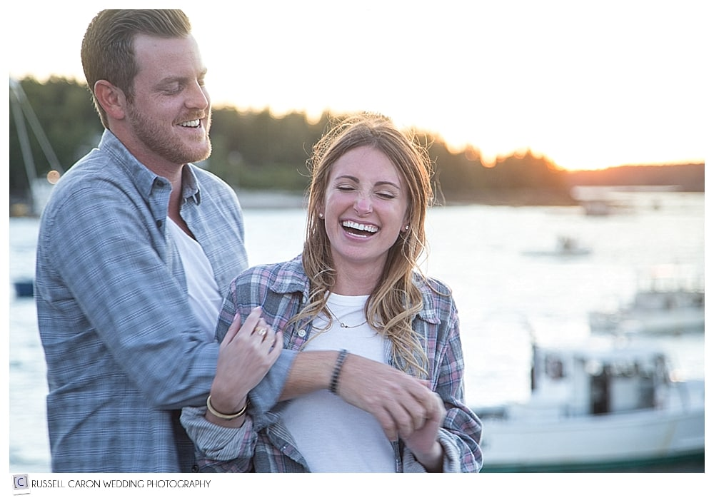 man and woman laughing together on fishing dock during Port Clyde engagement session