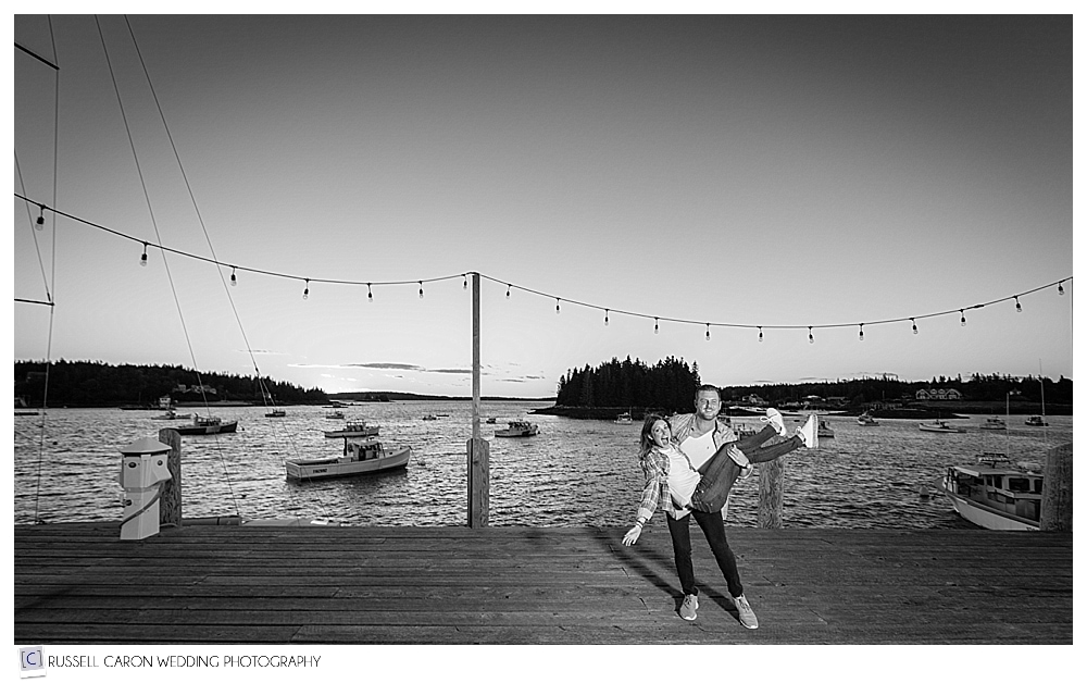 man holding woman on fishing dock, port clyde maine