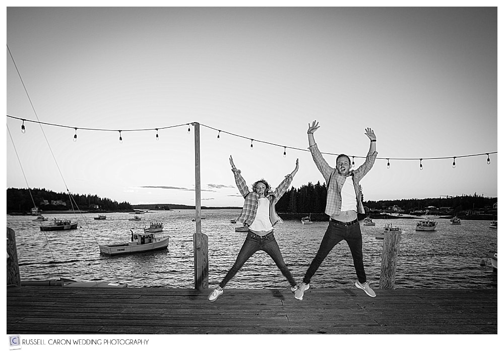 man and woman jumping in the air, on a fishing dock in port clyde maine