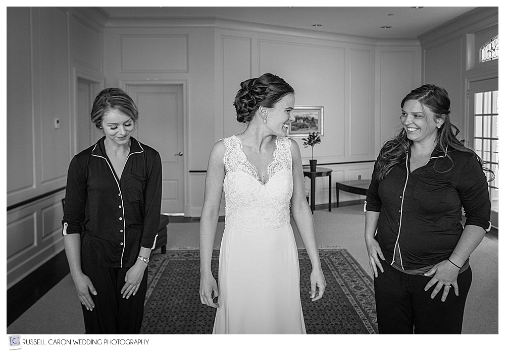bride getting into wedding dress with maid of honor and bridesmaid