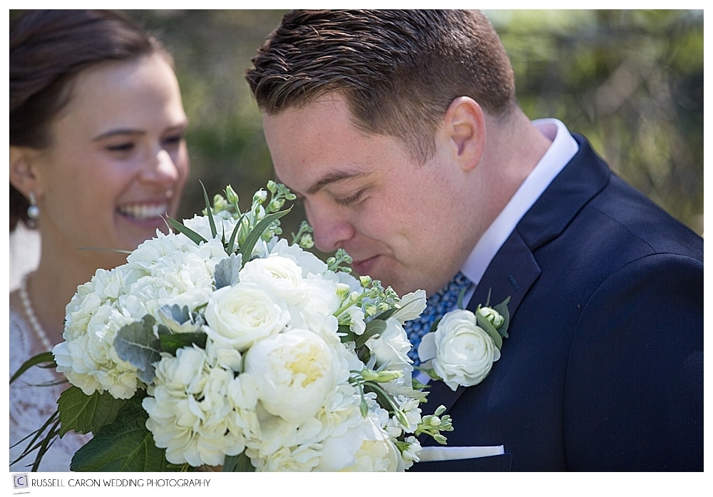 groom smelling bride's bouquet