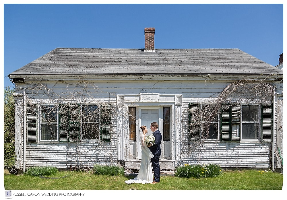 bride and groom in front of delapidated house in Camden Maine