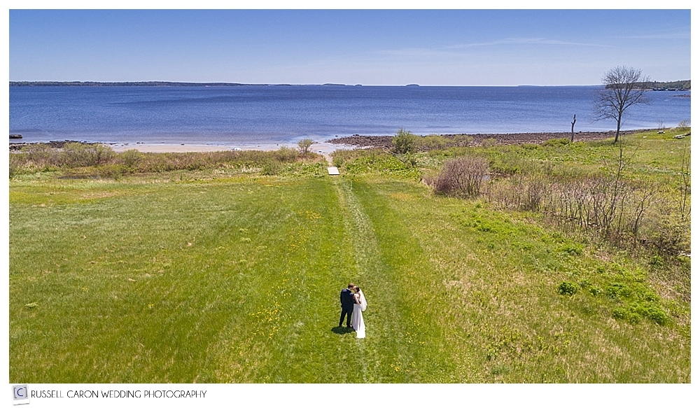 drone photo of bride and groom walking in field