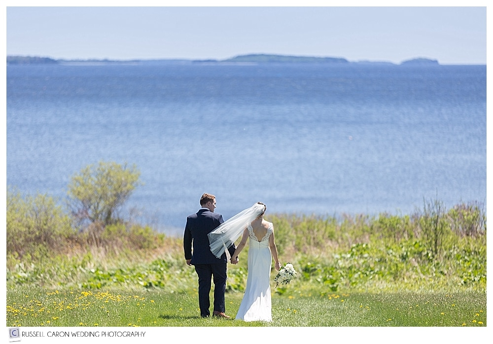 bride and groom walking towards the ocean during Northport Maine wedding
