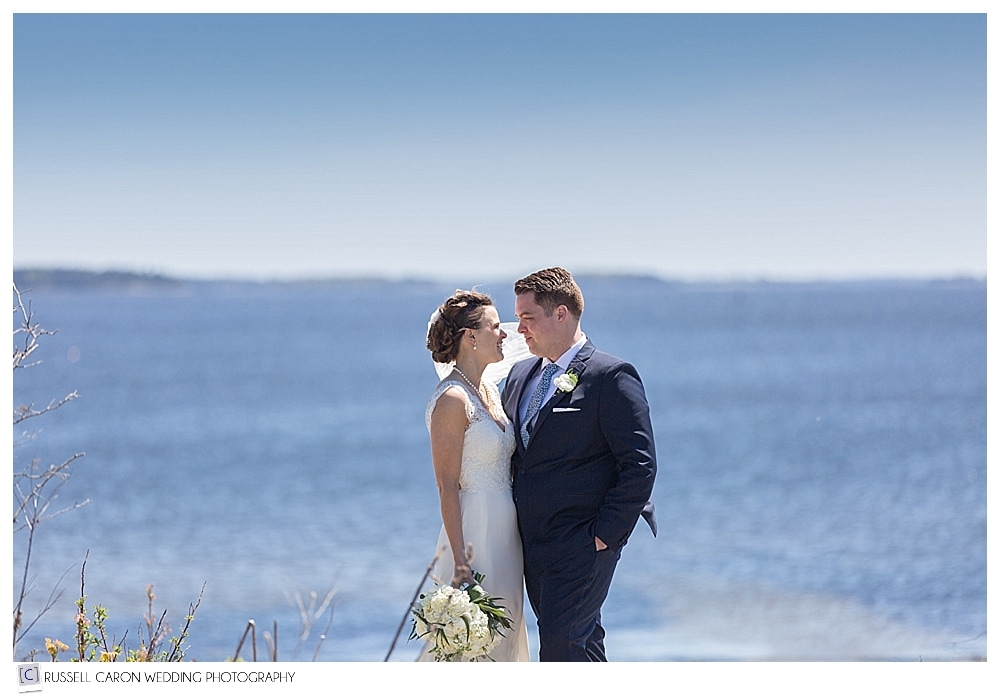 bride and groom standing together on Maine coast
