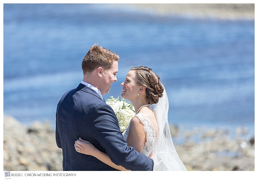 Bride and groom looking at each other while at the Maine coast