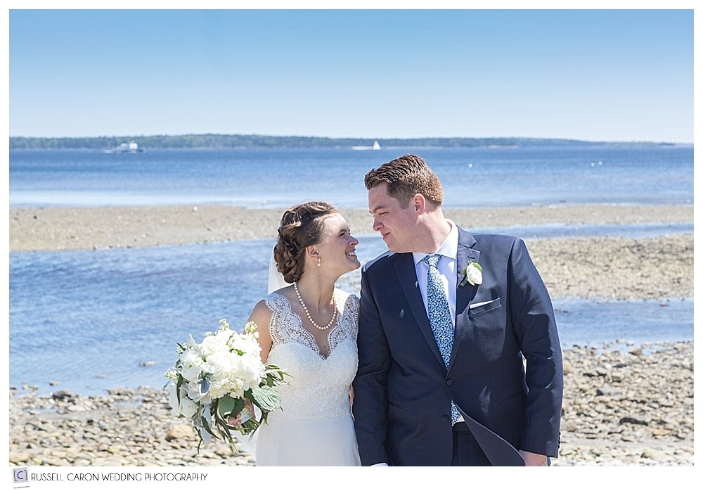 bride and groom walking on the beach during their Camden Maine wedding