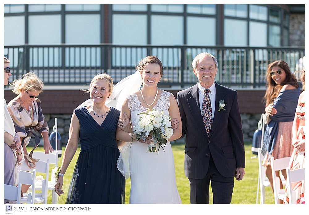 bride and parents walking down the aisle during outdoor wedding ceremony