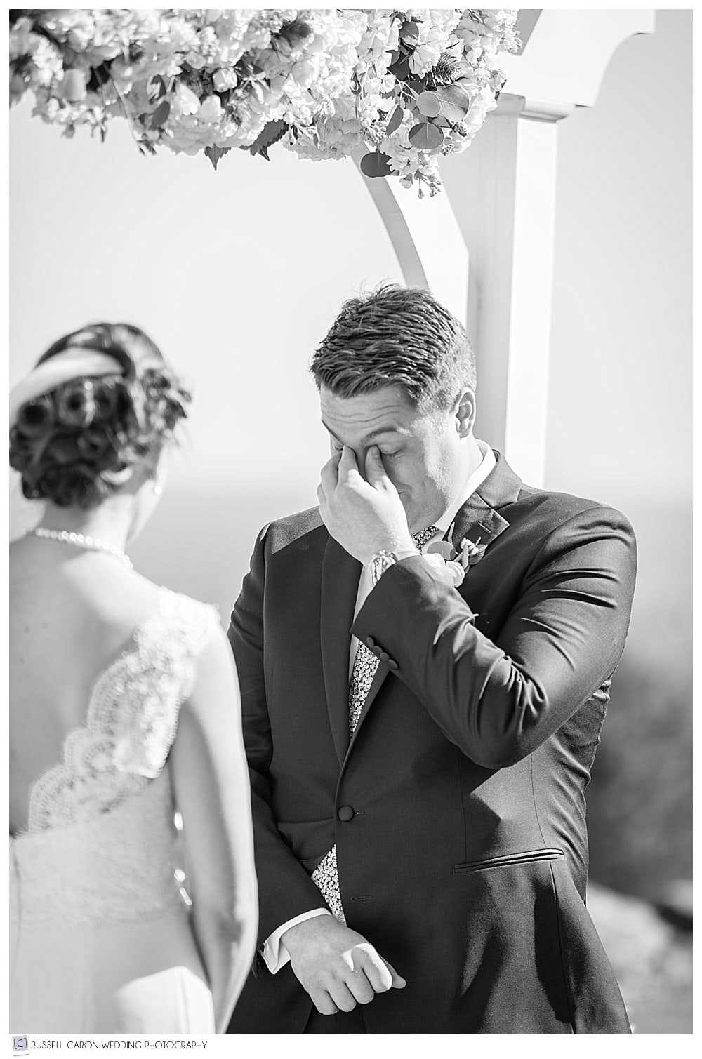 groom wiping eyes during wedding ceremony