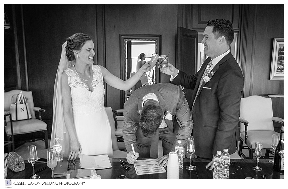 bride and groom toasting to each other while officiant signs marriage license