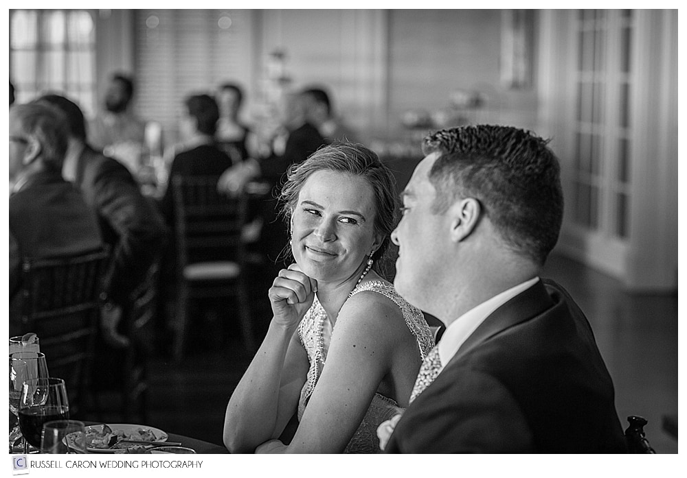 bride and groom smiling at each other during wedding reception