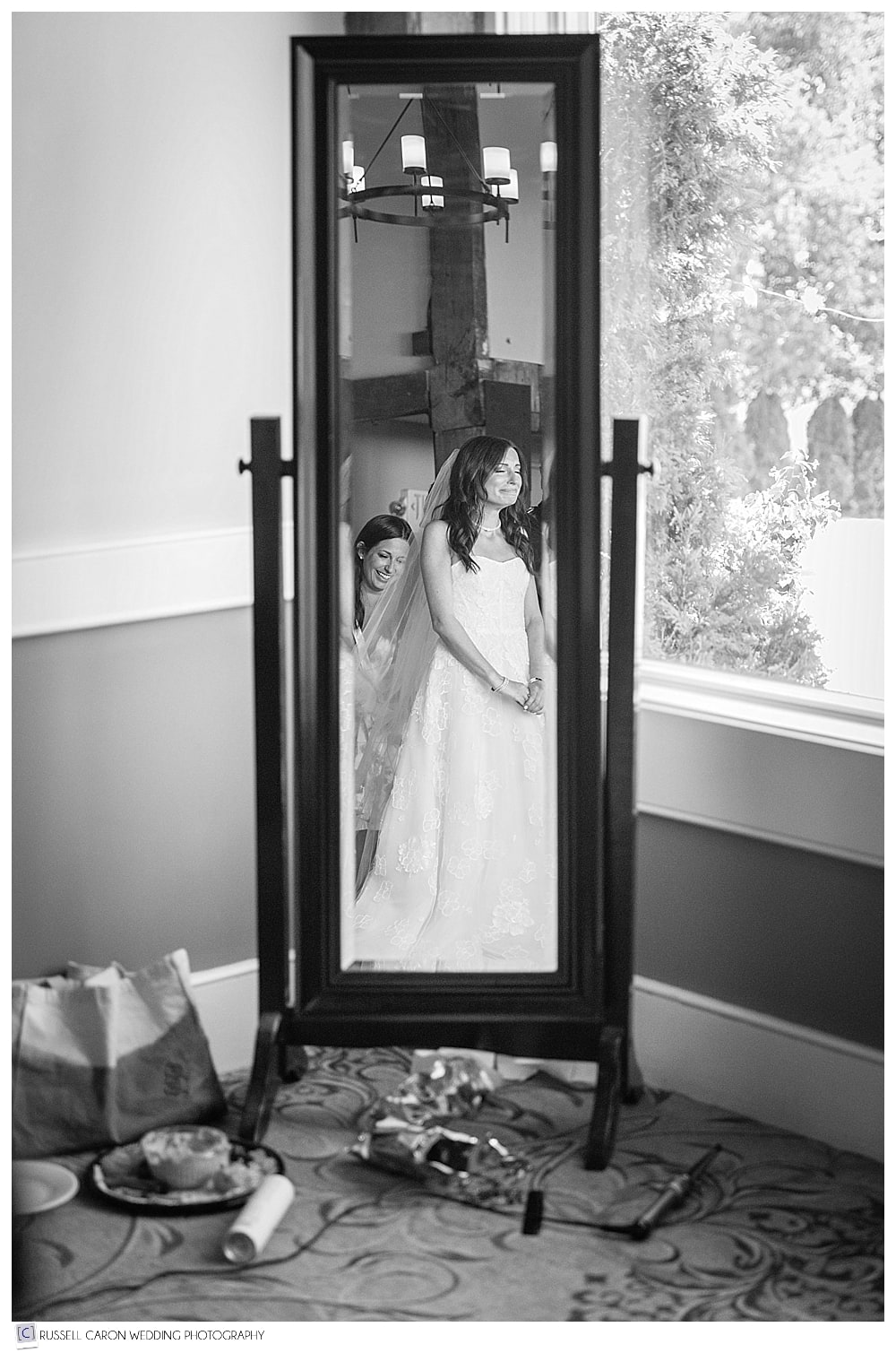 bride getting dressed, in the mirror