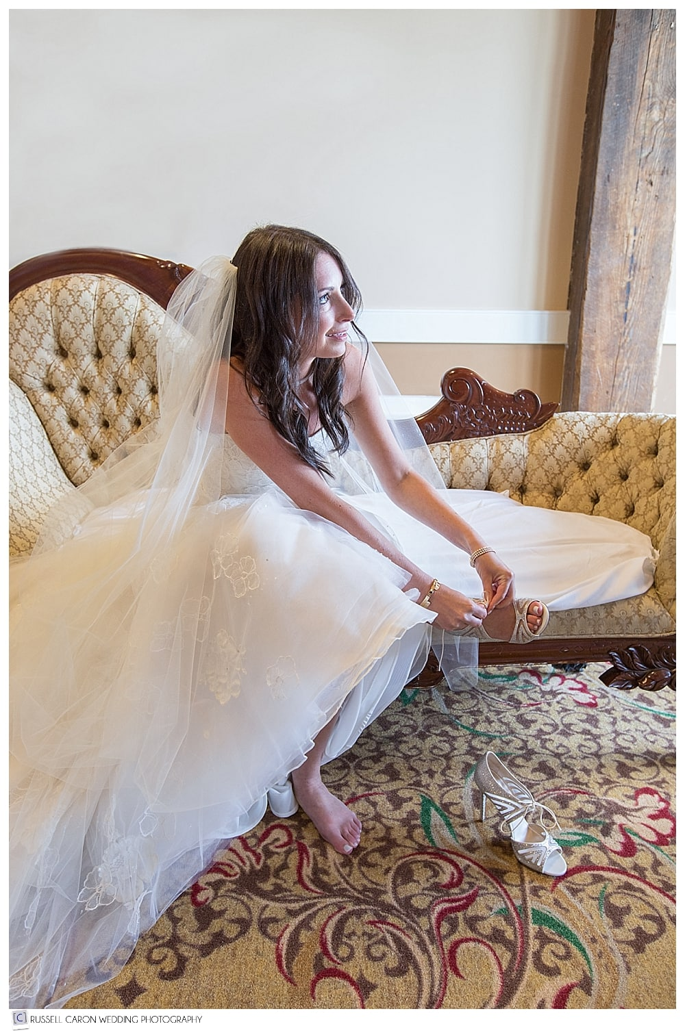 Bride sitting on settee, putting on shoes