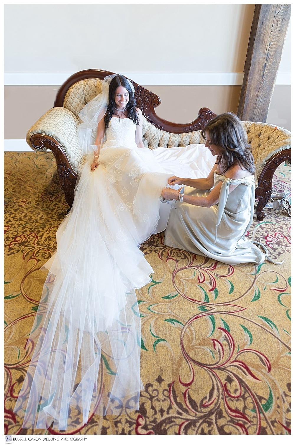 mother of the bride putting shoes on bride