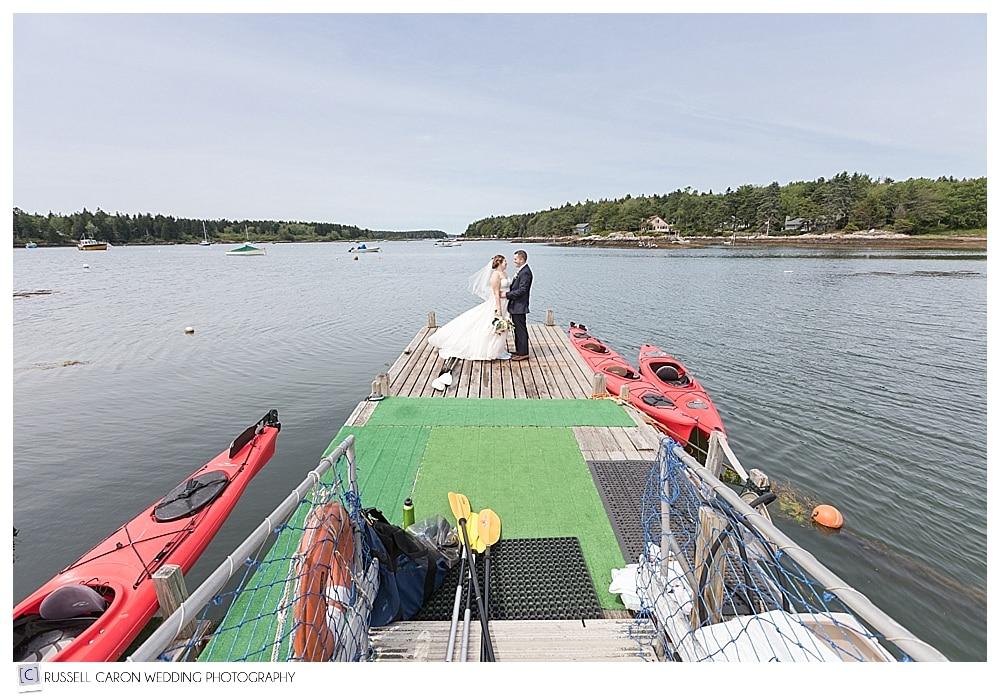 Bride and groom on the kayak dock at Sebasco Harbor wedding