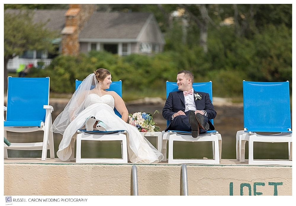 bride and groom sitting on chairs at the salt water pool at Sebasco Harbor Resort