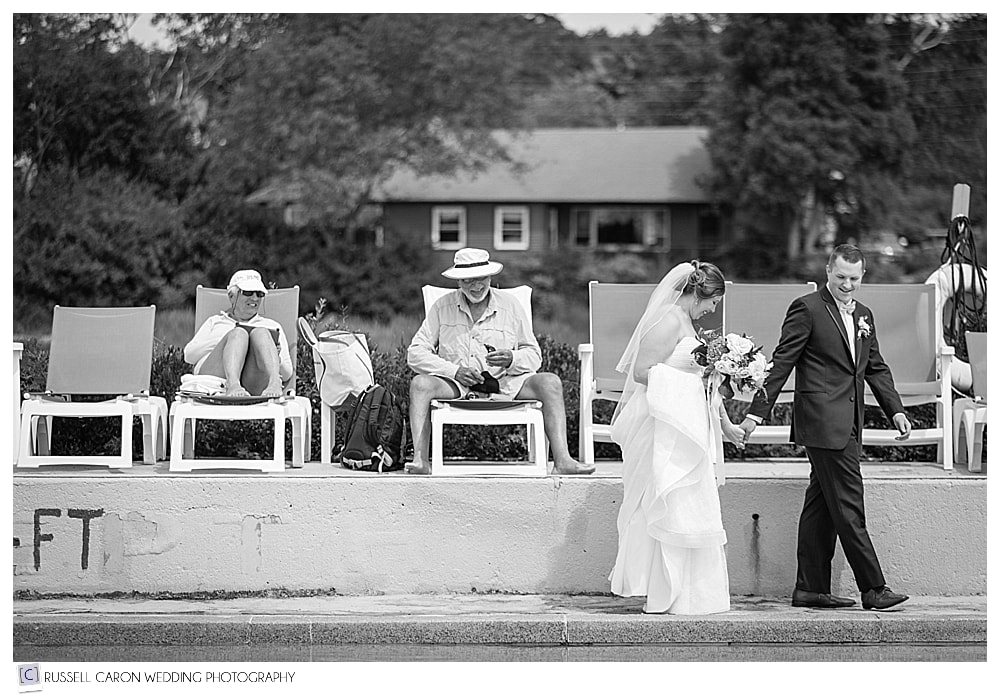 bride and groom walking along the edge of the pool