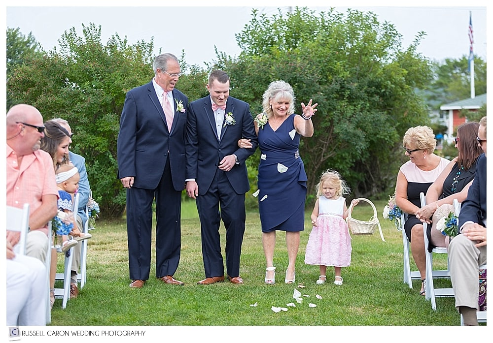 Groom, parents, and flower girl walking down the aisle