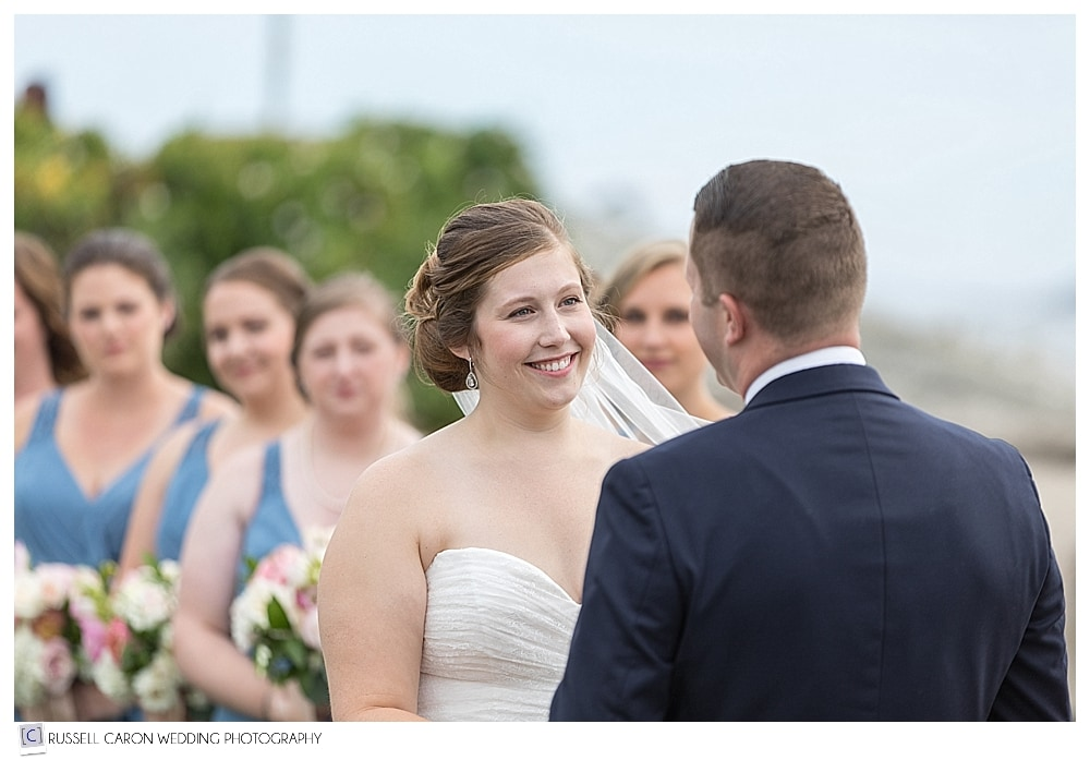 bride smiling at the groom during the wedding ceremony