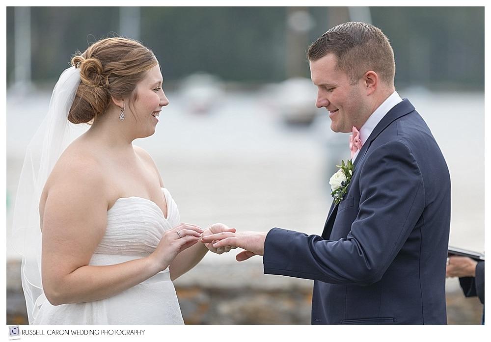 bride puts wedding band on groom's finger